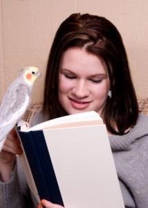Lány olvas,kezén ül a nimfapapagája