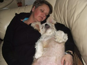 Nő és kutyája együtt pihennek a kanapén